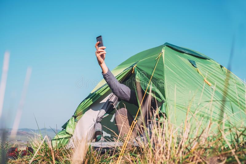 El viajero se sienta en tienda turística e intento para coger networ celular foto de archivo libre de regalías