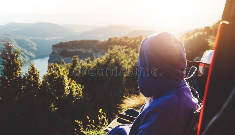El viajero turístico en la montaña superior del fondo sienta y disfruta de la puesta del sol, caminante que mira en las nubes del fotografía de archivo libre de regalías