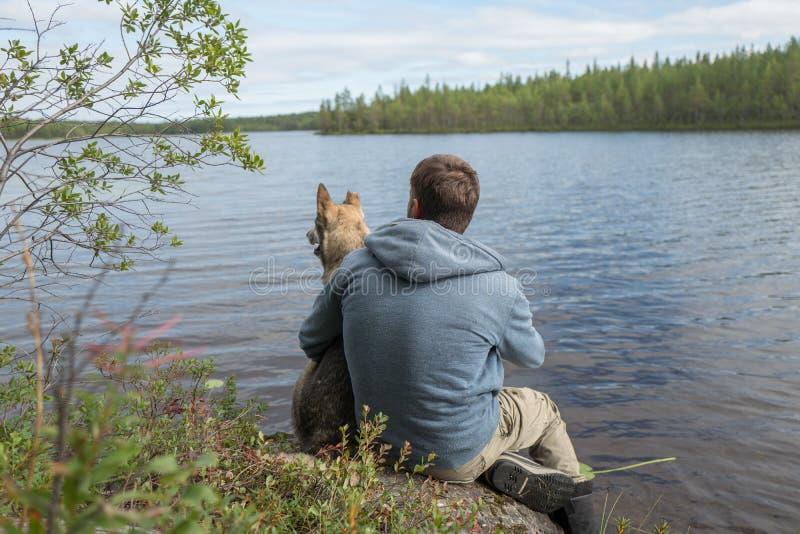 El viajero y el perro se están sentando en la orilla del lago y están mirando en la distancia foto de archivo