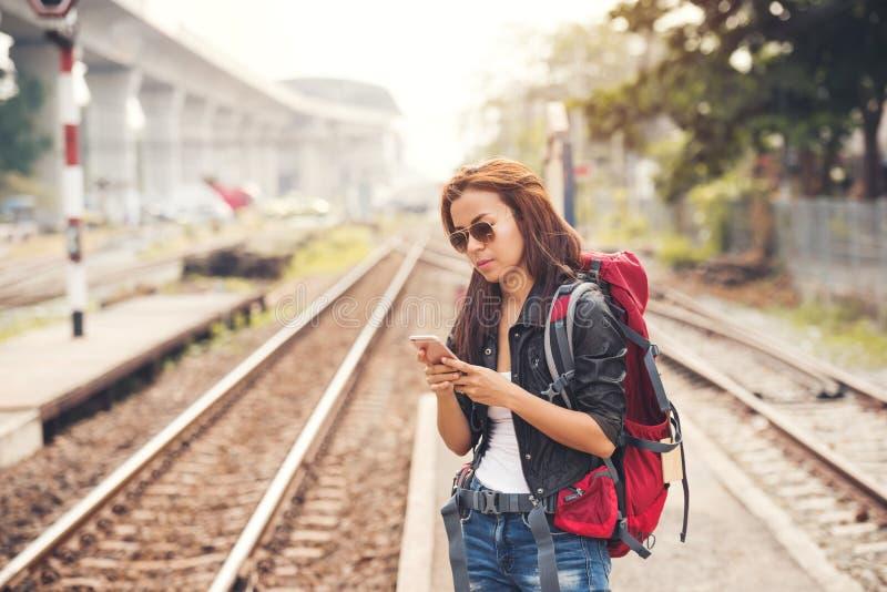 El viajero y la mochila de la mujer joven se colocan con usar smartphone en fotografía de archivo libre de regalías