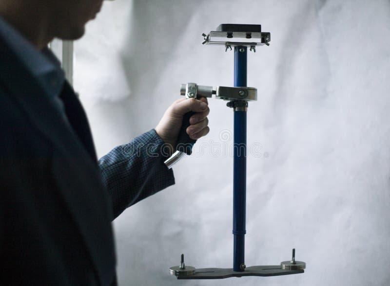 El videographer profesional guarda el steadicam con la cámara en el fondo blanco foto de archivo libre de regalías