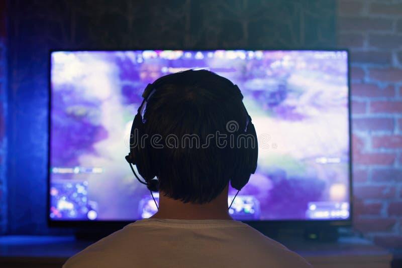 El videojugador o la flámula en auriculares con el micrófono se sienta en casa en sitio oscuro y juegos con los amigos en redes e foto de archivo libre de regalías