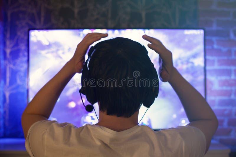 El videojugador o la flámula en auriculares con el micrófono se sienta en casa en sitio oscuro y juegos con los amigos en redes e fotografía de archivo libre de regalías