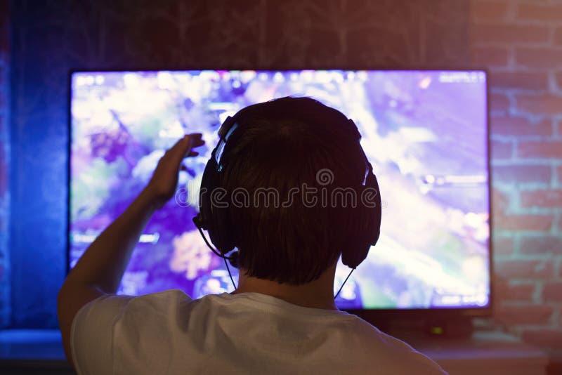 El videojugador o la flámula en auriculares con el micrófono se sienta en casa en sitio oscuro y juegos con los amigos en redes e imagen de archivo libre de regalías