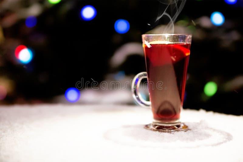 El vidrio con el vino reflexionado sobre se coloca en la calle en una tabla de la nieve en el fondo de las luces del ` s del Año  fotografía de archivo libre de regalías