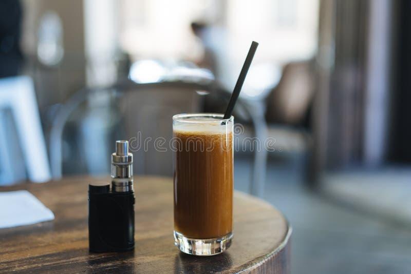 El vidrio de cóctel y un cigarrillo electrónico están en la tabla fotos de archivo