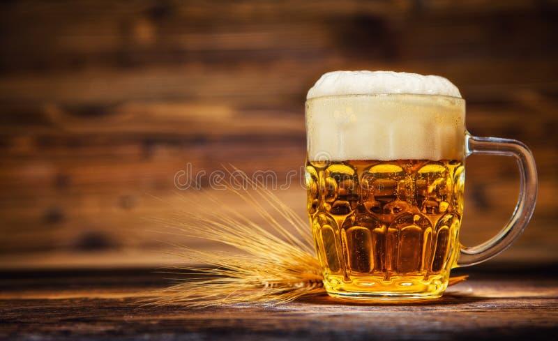 El vidrio de cerveza dorada sirvió en tablones de madera viejos, foto de archivo libre de regalías