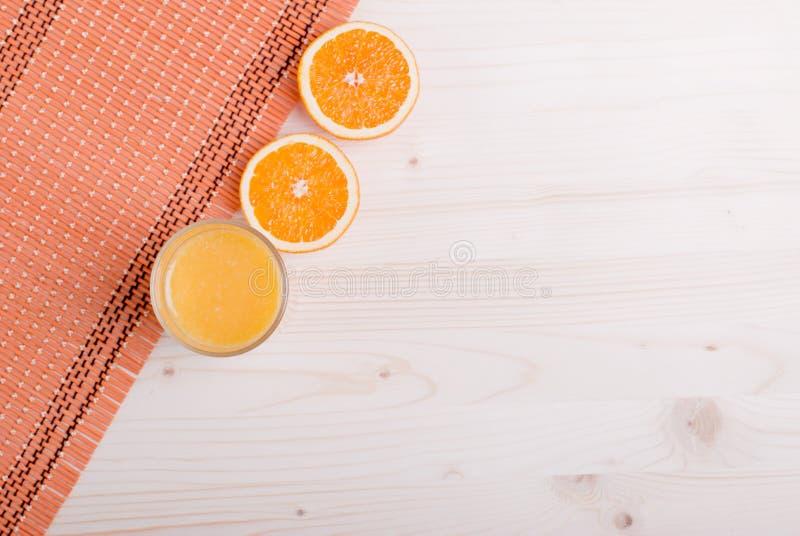 El vidrio de jugo fresco anaranjado en una tabla ligera y los oídos anaranjados rematan foto de archivo libre de regalías