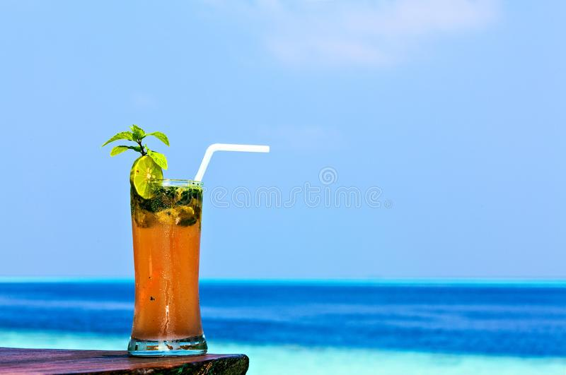 El vidrio de la bebida está en una tabla de la playa fotografía de archivo libre de regalías