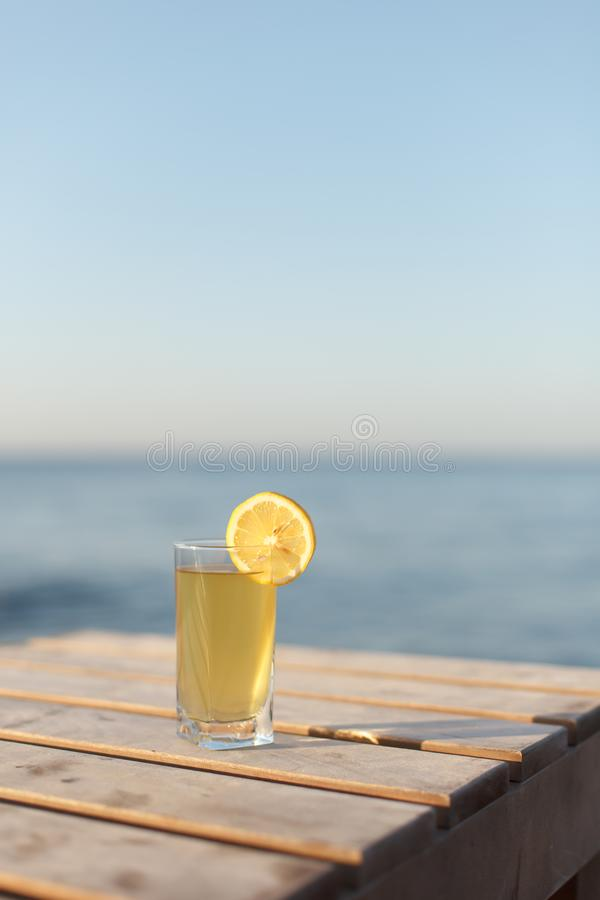 El vidrio de la bebida fría con el limón en la tabla sunbed o tabla en la playa imágenes de archivo libres de regalías