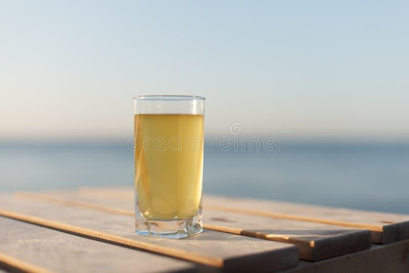 El vidrio de la bebida fría en la tabla sunbed o tabla en la playa imágenes de archivo libres de regalías