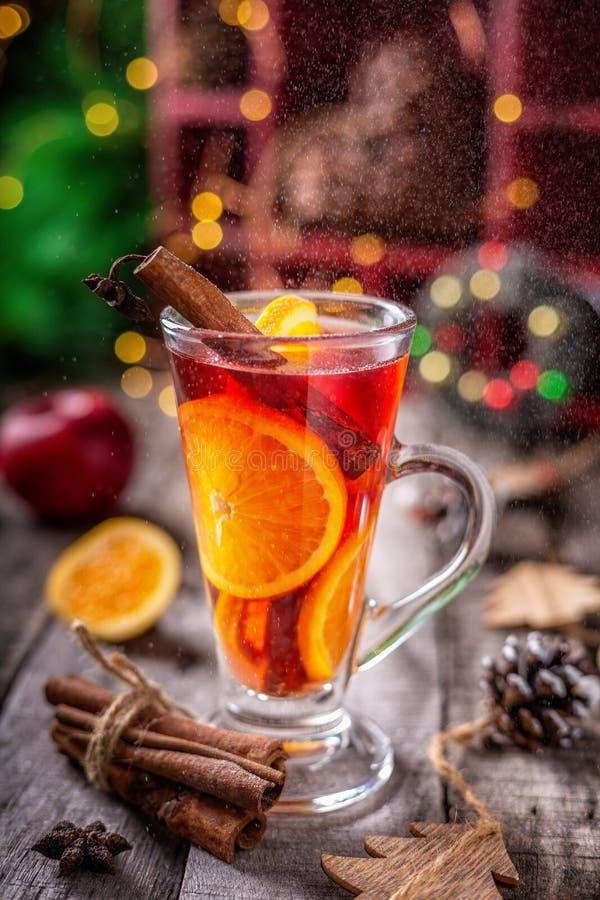 El vidrio de la Navidad reflexionó sobre el vino tinto con las especias y las frutas rodeadas por la decoración festiva, en una t foto de archivo libre de regalías