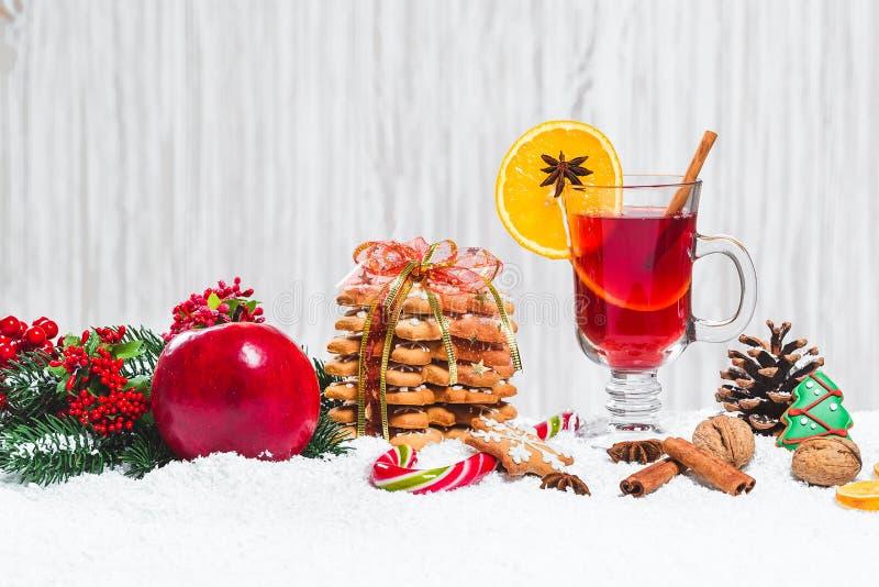 El vidrio de la Navidad de rojo reflexionó sobre el vino en la tabla con los palillos de canela, ramas del árbol de navidad, niev imagenes de archivo