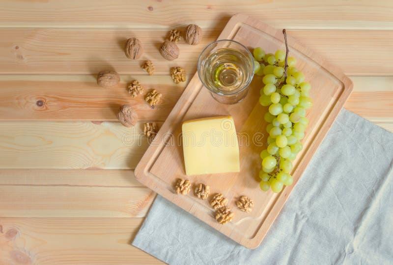 El vidrio de vino blanco, el queso parmesano, las nueces y la uva ramifican en la tabla de madera fotografía de archivo