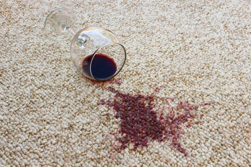 El vidrio de vino rojo cayó en la alfombra foto de archivo