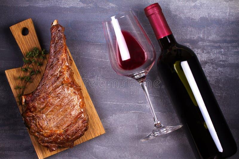 El vidrio de vino rojo y la costilla observan el filete de carne de vaca imágenes de archivo libres de regalías