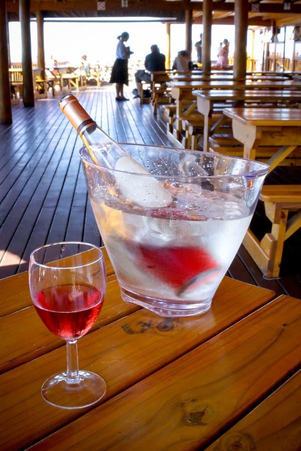El vidrio de vino y la botella refrescada adentro bucked en restaura imagen de archivo libre de regalías