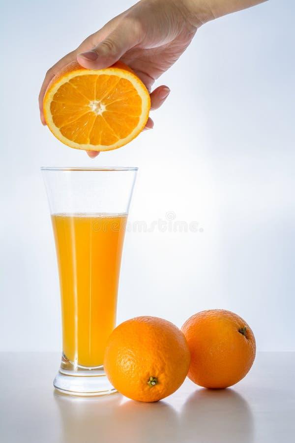 El vidrio de zumo de naranja fresco y la mujer dan sostener la fruta anaranjada fotografía de archivo libre de regalías