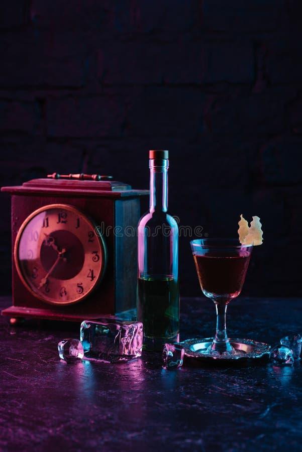 el vidrio del cóctel del alcohol, la botella de licor y el vintage registran fotos de archivo libres de regalías
