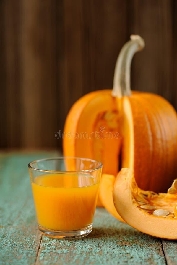 El vidrio del jugo dulce de la calabaza y de la calabaza cortada junta las piezas con las semillas o foto de archivo libre de regalías