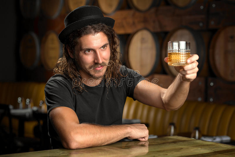 El vidrio del whisky anima el borbón de consumición del hombre elegante en una barra del restaurante de la destilería del whisky fotos de archivo