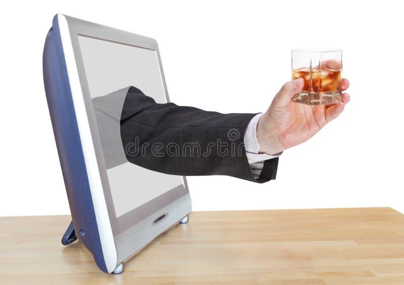 El vidrio del whisky en mano del hombre de negocios inclina hacia fuera la TV fotografía de archivo