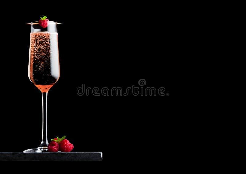 El vidrio elegante de champán de la rosa del rosa con la frambuesa en el palillo con las bayas frescas y la menta hojean en table imagen de archivo libre de regalías