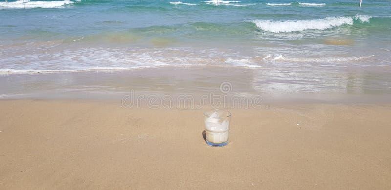 el vidrio transparente del caf? se coloca en arena mojada fotografía de archivo libre de regalías