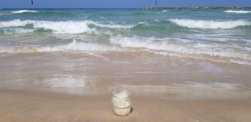 El vidrio transparente vacío del café se coloca en arena mojada foto de archivo
