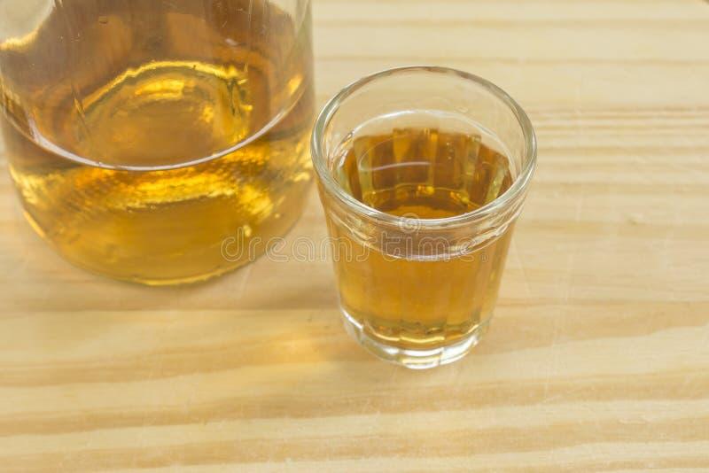 El vidrio y la botella de licor brasileño de la caña de azúcar llamaron cachaca imagen de archivo libre de regalías