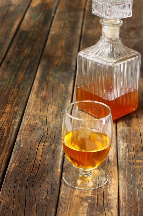 El vidrio y la botella de licor tienen gusto escocés, borbón, whisky o brandy en la tabla de madera imagenes de archivo