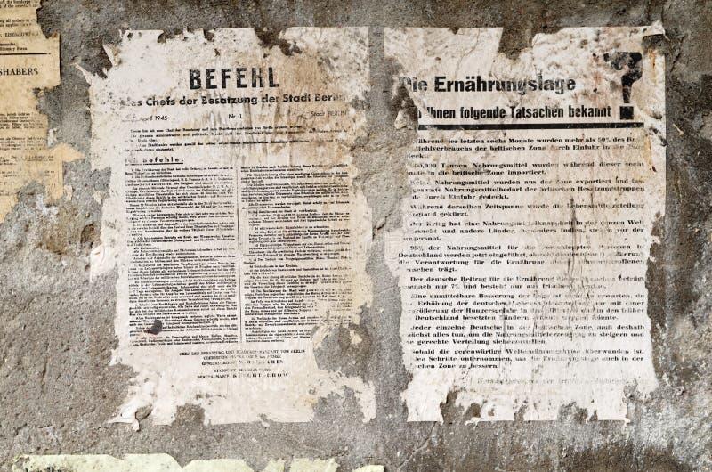 El viejo alemán dañó noticias del periódico del cartel en una pared stock de ilustración