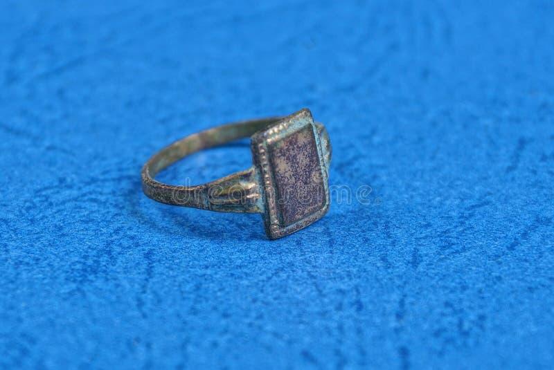 El viejo anillo lamentable amarillo miente en una tabla azul foto de archivo