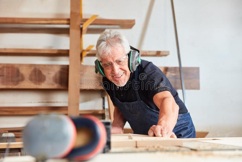 El viejo carpintero asierra la madera en la sierra de circular fotos de archivo