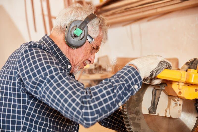 El viejo carpintero asierra la madera en la tajada vio imagenes de archivo