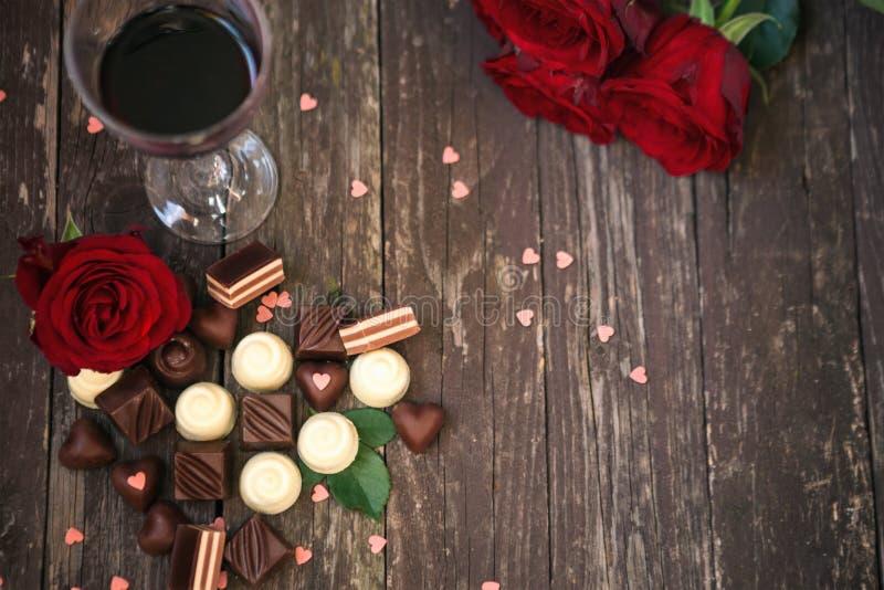 El viejo fondo de madera con las rosas rojas y las almendras garapiñadas del chocolate copian fotografía de archivo libre de regalías