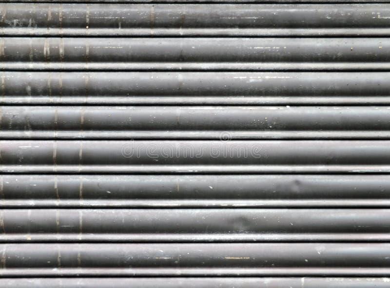 El viejo gris sucio manchó los obturadores cerrados horizontales de la seguridad del laminado de acero foto de archivo libre de regalías