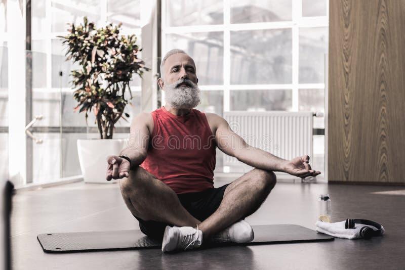 El viejo hombre agradable está disfrutando de yoga en centro de aptitud fotos de archivo