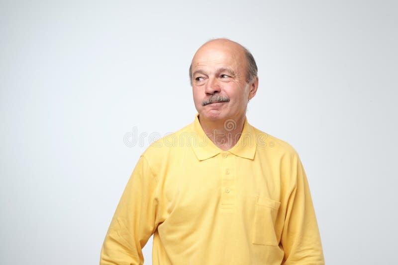 El viejo hombre atractivo maduro en la camisa amarilla con mirada escéptica, ceja de los aumentos en el desconcierto, tiene algun imagen de archivo libre de regalías