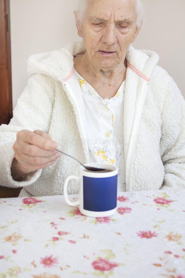 El viejo hombre canoso se sienta en la tabla y toma una taza de té de una cucharilla fotografía de archivo