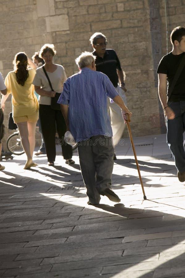 El viejo hombre con el bastón camina abajo de la vieja sección apretada de Barcelona, España, en el área de Barri Gotic que tambi imagen de archivo libre de regalías