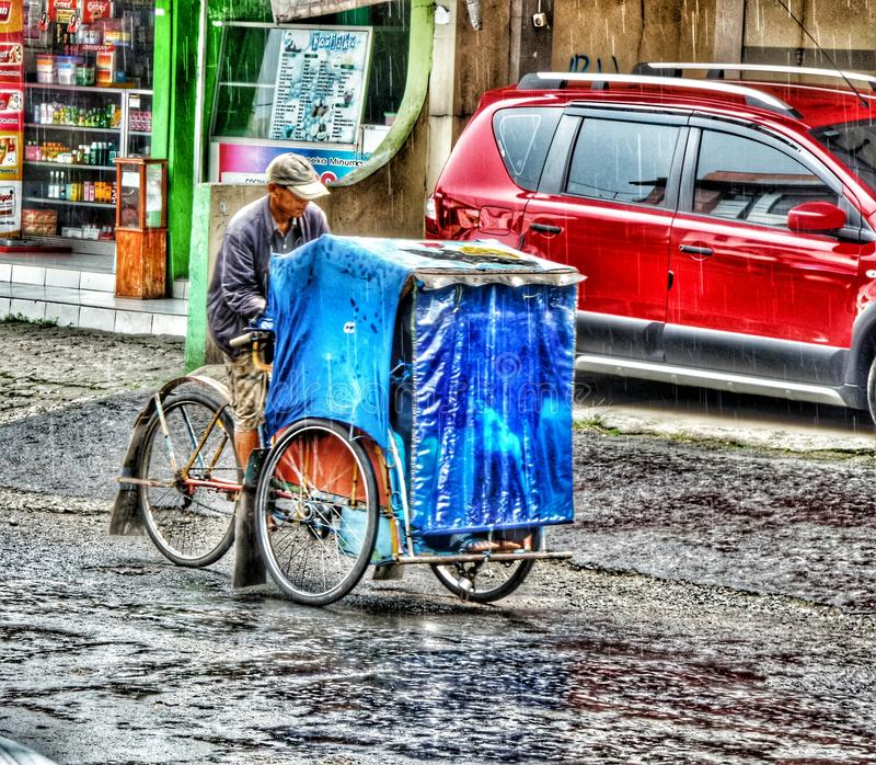 el viejo hombre con el tren en la lluvia de la calle imagen de archivo libre de regalías