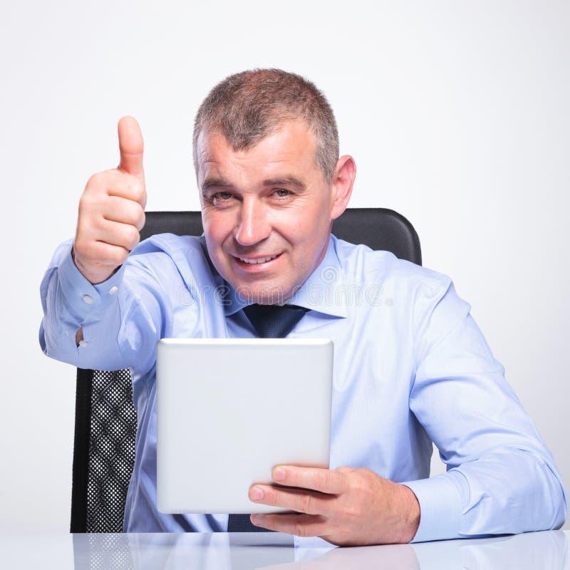 El viejo hombre de negocios con el cojín muestra el pulgar para arriba fotos de archivo libres de regalías