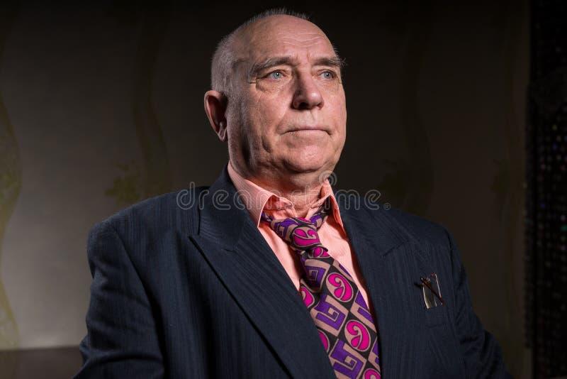 El viejo hombre de negocios hermoso se está sentando en su sitio imagen de archivo libre de regalías