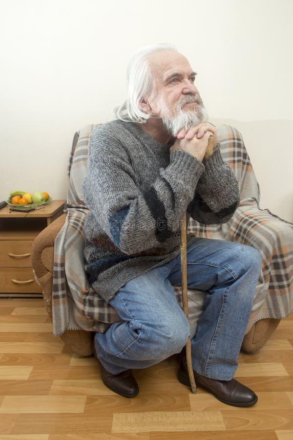 El viejo hombre en la butaca en casa fotografía de archivo
