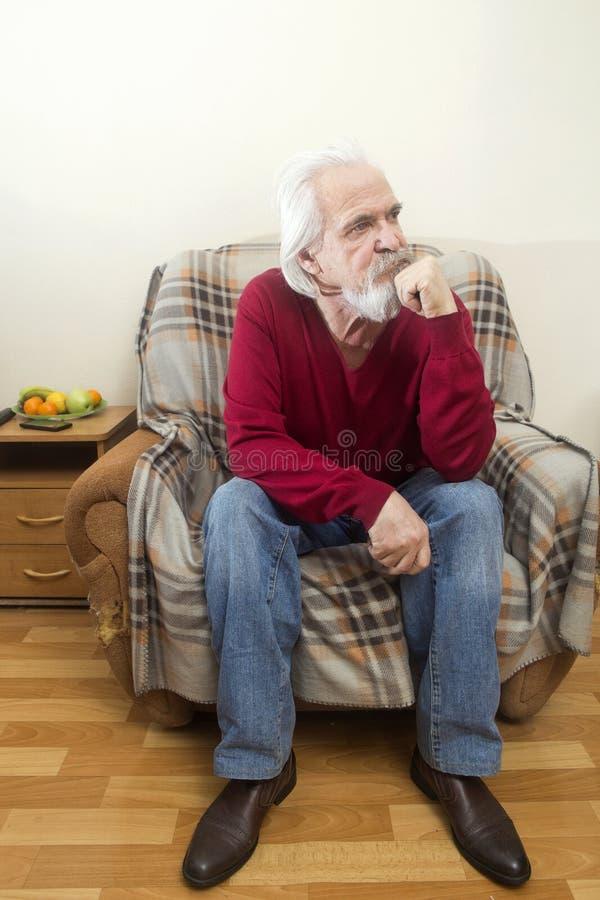 El viejo hombre en la butaca en casa imágenes de archivo libres de regalías