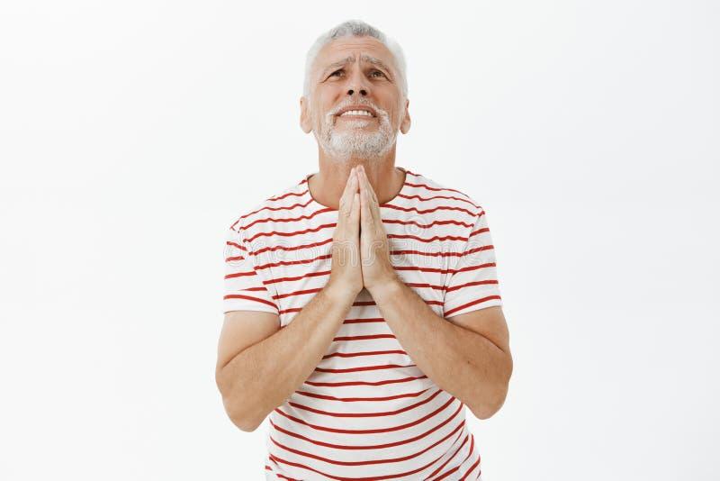 El viejo hombre esperanzado en camiseta rayada que lleva de la necesidad y del problema con la barba gris que lleva a cabo las ma foto de archivo libre de regalías