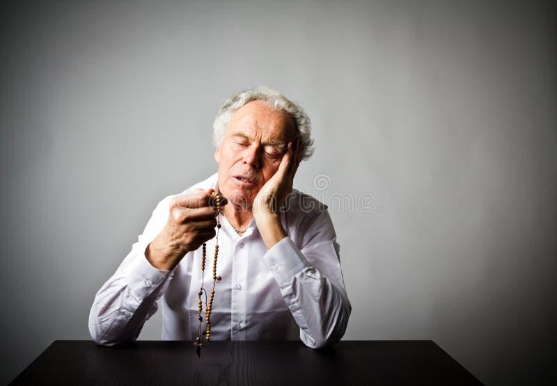 El viejo hombre está rogando con las gotas del rosario imagen de archivo
