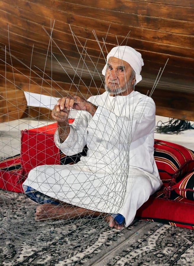 El viejo hombre está tejiendo una red de pesca para encontrar a huéspedes en el pavil fotografía de archivo
