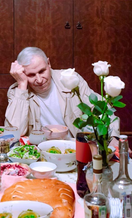 El viejo hombre está triste después del banquete del día de fiesta fotos de archivo